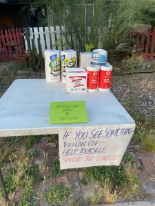 table with paper goods and a sign that says if you see something you can use help yourself